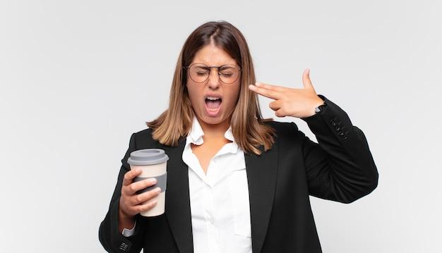 Giovane donna di affari con un caffè che sembra infelice e stressato, gesto di suicidio che fa il segno della pistola con la mano, indicando la testa