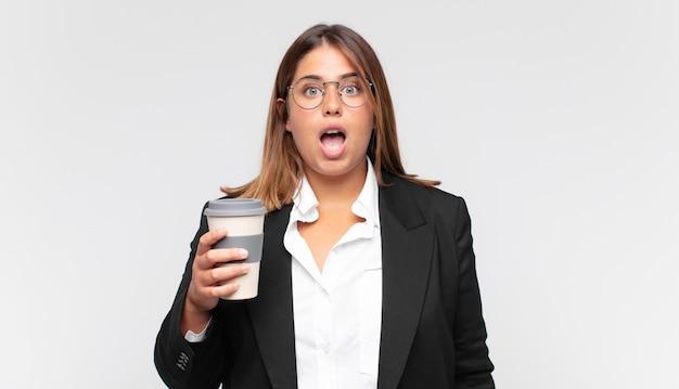Giovane imprenditrice con un caffè che sembra molto scioccata o sorpresa