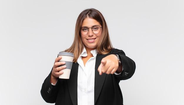 Giovane imprenditrice con un caffè che punta alla telecamera con un sorriso soddisfatto, fiducioso, amichevole, scegliendo te