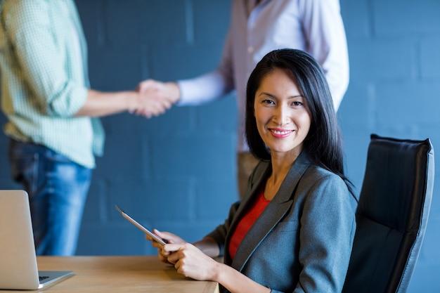 Giovane imprenditrice con i colleghi si stringono la mano