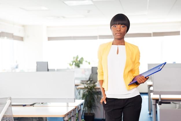 Giovane imprenditrice con cartella in piedi in ufficio