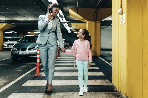 Giovane imprenditrice con sua figlia in un garage sotterraneo pubblico.