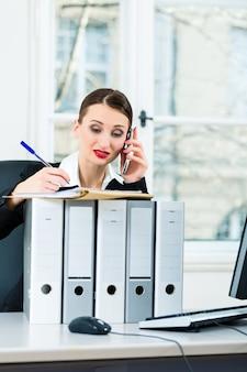 Giovane imprenditrice che lavora nel suo ufficio, si siede dietro le cartelle e al telefono è un cliente o un cliente