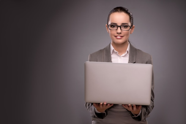 Giovane donna di affari che lavora con il computer portatile nel concetto di affari
