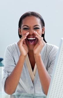 Giovane imprenditrice urlando alla sua scrivania