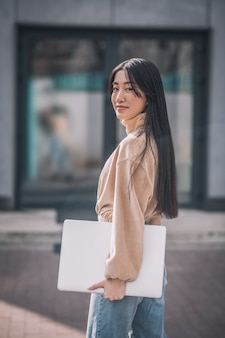 Giovane imprenditrice. giovane donna asiatica che tiene un computer portatile e che sembra sicura