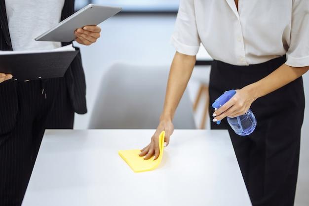 Giovani donne di affari puliscono il posto di lavoro, asciugano la scrivania con uno straccio giallo. i colleghi disinfettano la superficie di lavoro con uno spray disinfettante per fermare la diffusione del covid-19.
