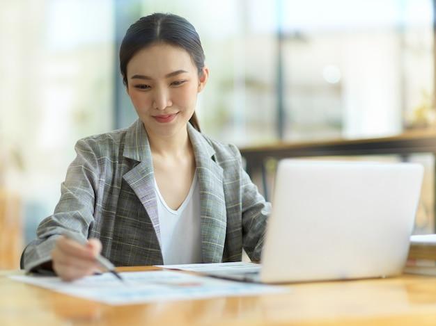 Responsabile finanziario delle giovani donne d'affari che lavora al computer portatile, guardando i fogli di calcolo finanziari sul tavolo di lavoro in ufficio