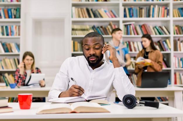 Giovane uomo africano impegnato in camicia bianca, studente che studia in biblioteca all'università, parlando sullo smartphone e prendendo appunti nel suo quaderno