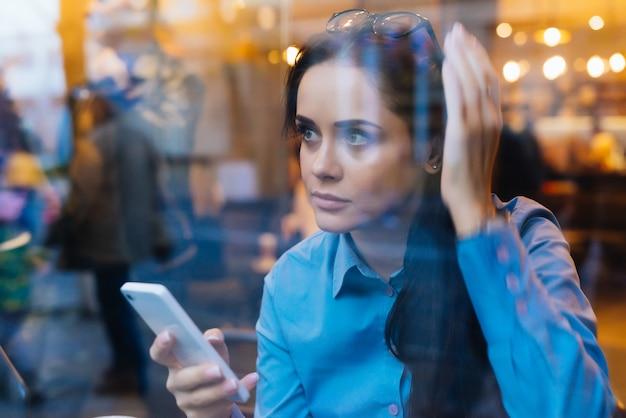 La giovane ragazza impegnata in una camicia blu è seduta in un caffè, tiene in mano uno smartphone