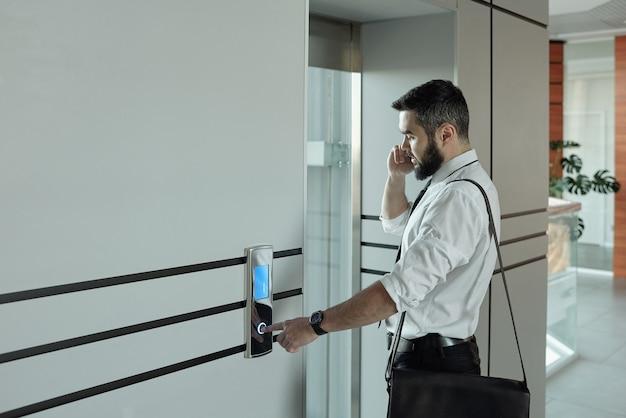 Giovane manager di ufficio occupato con lo smartphone a parlare con il cliente mentre è in piedi in ascensore e premendo il pulsante di chiamata