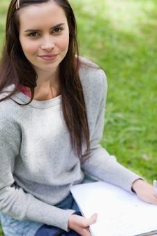 Giovane ragazza calma che si siede in una sosta mentre tengono i libri di banco