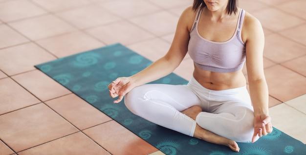 Giovane donna calma yogi meditando in studio di yoga.