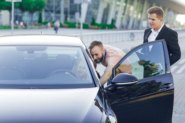 Un giovane concessionario di automobili in giacca e cravatta mostra agli acquirenti un'auto nuova. una giovane coppia, uomo e donna, compra un'auto. felice donna seduta al volante. acquisto di macchine, giro di prova.