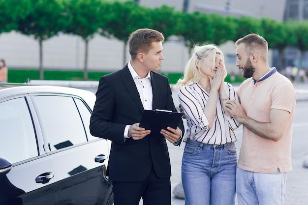 Un giovane concessionario di automobili in giacca e cravatta mostra agli acquirenti un'auto nuova. una giovane coppia, uomo e donna, compra un'auto. acquisto di macchine, giro di prova.
