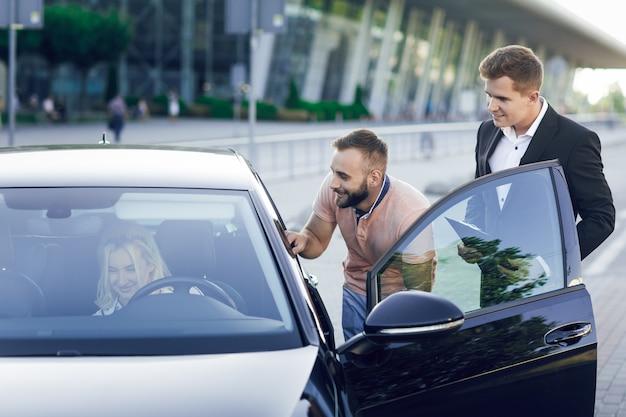 Un giovane concessionario di automobili in giacca e cravatta mostra agli acquirenti un'auto nuova. una giovane coppia, uomo e donna, compra un'auto. donna seduta al volante. acquisto di macchine, giro di prova.