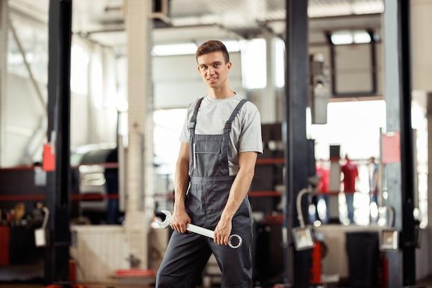 Un giovane meccanico è in piedi con una chiave inglese in mano.