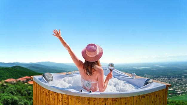 Giovane viaggiatrice spensierata che si rilassa con un bicchiere di vino al tubo caldo durante il godersi la vita di vacanza del momento di viaggio felice sullo sfondo delle grandi montagne verdi