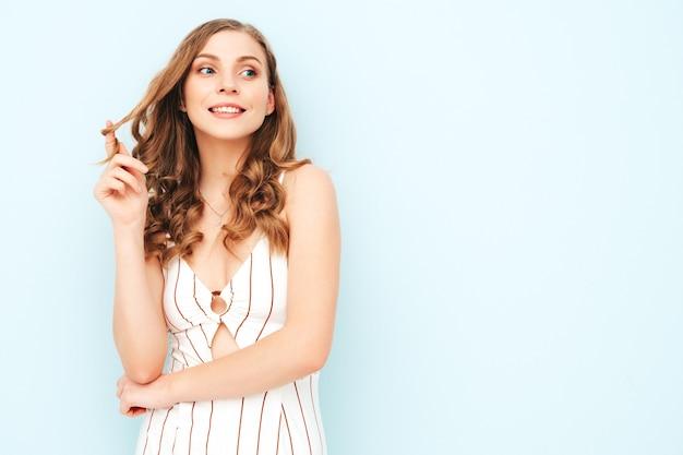 Giovane donna spensierata che posa vicino alla parete blu-chiaro in studio