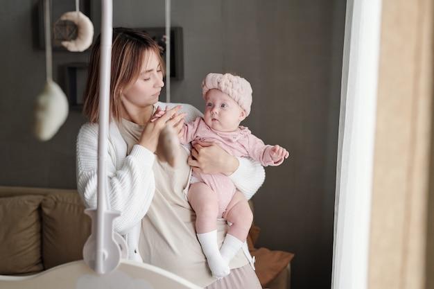 Giovane madre attenta che guarda la sua adorabile figlia