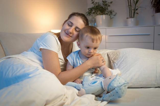 Giovane madre premurosa che abbraccia il suo bambino sul letto di notte