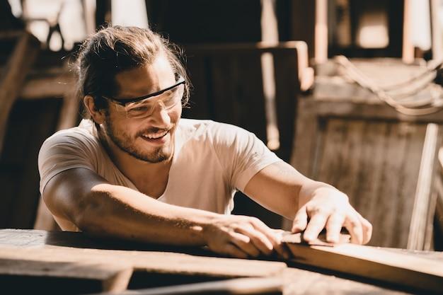 Il giovane falegname lavora felicemente per rendere i mobili di artigianato del legno nell'officina del legno un operaio professionale di alta abilità.