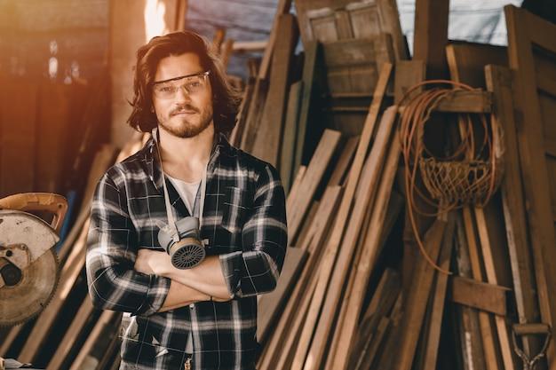 Giovani falegnami uomo falegname di nuova generazione di affari che fa mobili. ritratto di woodcraft maschio in piedi braccio incrociato in officina del legno.