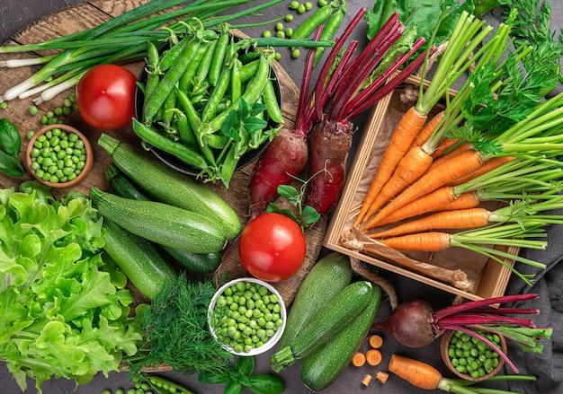Giovani carote, zucchine, pomodori, piselli e verdure su uno sfondo marrone. vista dall'alto, primo piano.