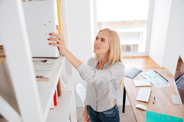 Giovane donna d'affari casual che prende la cartella da uno scaffale di libri in piedi in ufficio