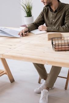 Giovane imprenditore casual o studente guardando attraverso l'articolo nella rivista e prendere appunti mentre si preparano i compiti