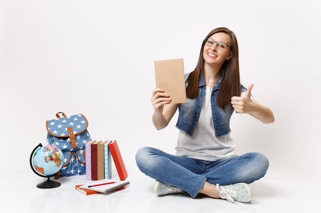 Giovane studentessa casual allegra in abiti di jeans con in mano un libro che mostra pollice in su seduto vicino a globo, zaino, libri di scuola