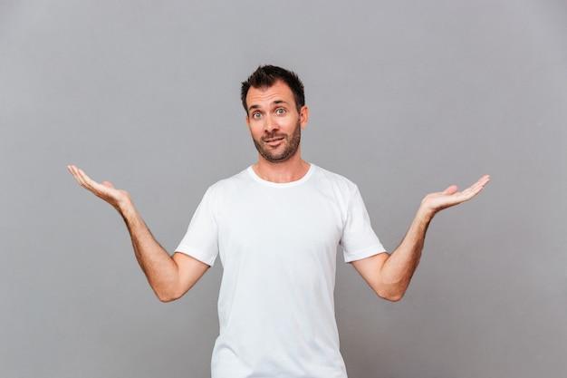 Giovane uomo casual in piedi e tenendo copyspace su entrambi i palmi su sfondo grigio