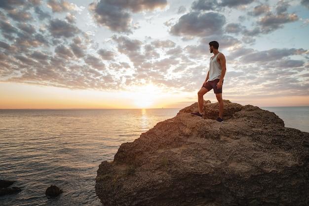 Giovane uomo casual in piedi sulla roccia di montagna in riva al mare e guardando il tramonto