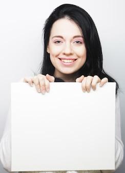 Segno in bianco felice della tenuta della giovane donna casuale