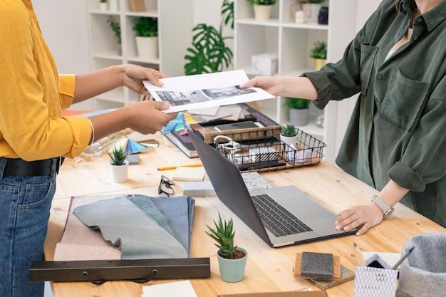Giovane donna casuale che passa carta con la fotografia della stanza all'interior designer femminile sul suo posto di lavoro mentre fa l'ordine