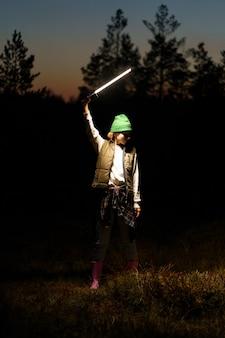 Giovane donna casual in posa con lampada fotografica a led nel crepuscolo nella foresta durante la sessione fotografica di moda notturna