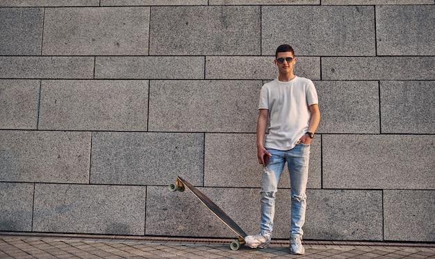 Giovane ragazzo americano caucasico con gli occhiali con un longboard contro il muro grigio di un edificio urbano