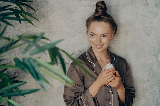 Giovane donna caucasica attraente in pigiama marrone di seta che fa la procedura di cura della pelle a casa