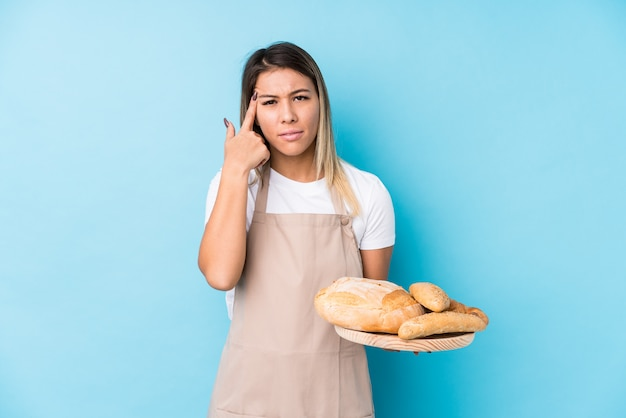 La giovane donna caucasica del panettiere ha isolato mostrando un gesto di delusione con l'indice.