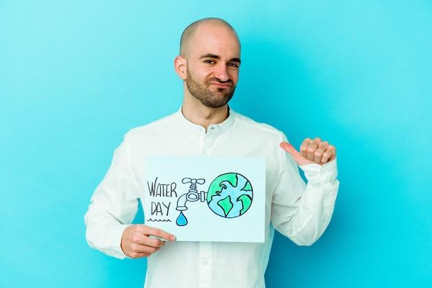 Il giovane uomo calvo caucasico che celebra la giornata mondiale dell'acqua isolata su sfondo blu si sente orgoglioso e sicuro di sé