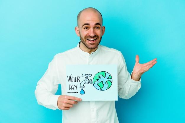 Giovane uomo calvo caucasico che celebra la giornata mondiale dell'acqua isolata su sfondo blu che riceve una piacevole sorpresa