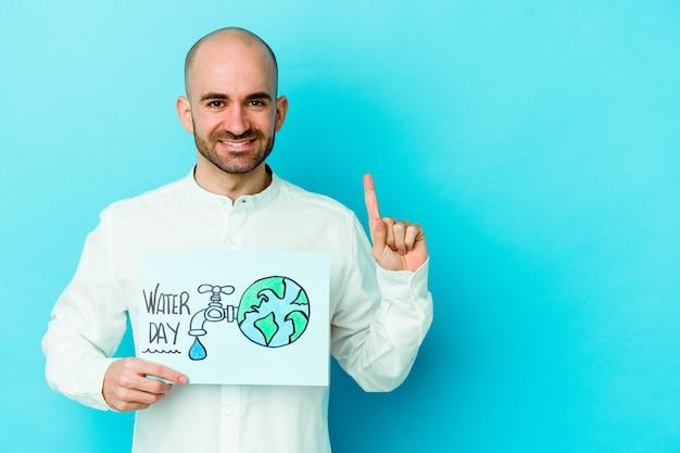 Giovane uomo calvo caucasico che celebra la giornata mondiale dell'acqua isolato su sfondo blu che mostra il numero uno