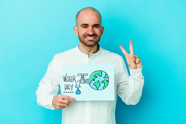 Giovane uomo calvo caucasico che celebra la giornata mondiale dell'acqua isolato su sfondo blu che mostra il numero due