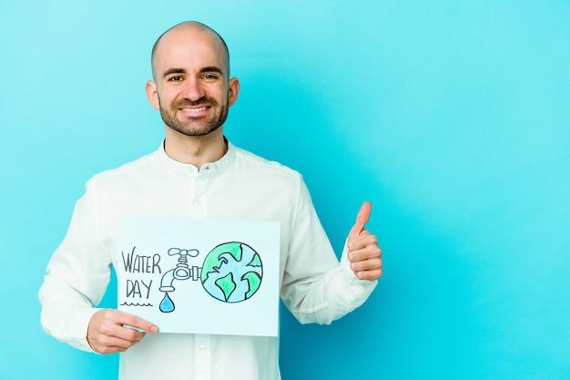 Giovane uomo calvo caucasico che celebra la giornata mondiale dell'acqua isolato su sfondo blu