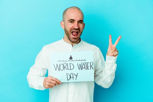 Giovane uomo calvo caucasico che celebra la giornata mondiale dell'acqua isolato su blu gioioso e spensierato che mostra un simbolo di pace con le dita.