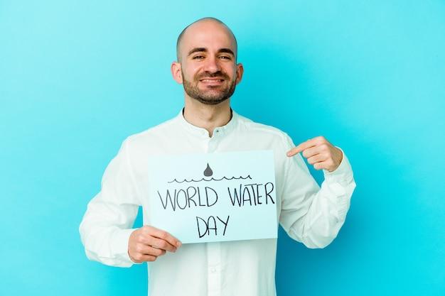 Giovane uomo calvo caucasico che celebra la giornata mondiale dell'acqua isolata sulla persona blu che punta a mano uno spazio di copia della camicia, orgoglioso e fiducioso