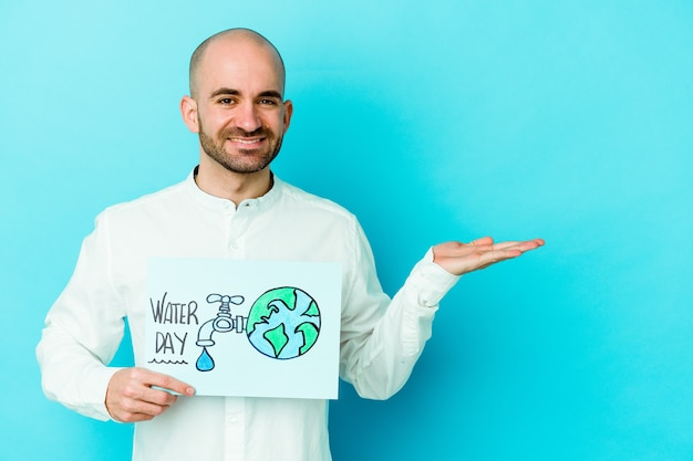 Giovane uomo calvo caucasico che celebra la giornata mondiale dell'acqua isolata sull'azzurro che mostra uno spazio della copia su una palma e che tiene un'altra mano sulla vita.