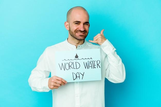 Giovane uomo calvo caucasico che celebra la giornata mondiale dell'acqua isolata sul blu che mostra un gesto di chiamata di cellulare con le dita