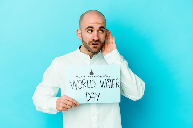 Giovane uomo calvo caucasico che celebra la giornata mondiale dell'acqua isolata sull'azzurro cercando di ascoltare un pettegolezzo.