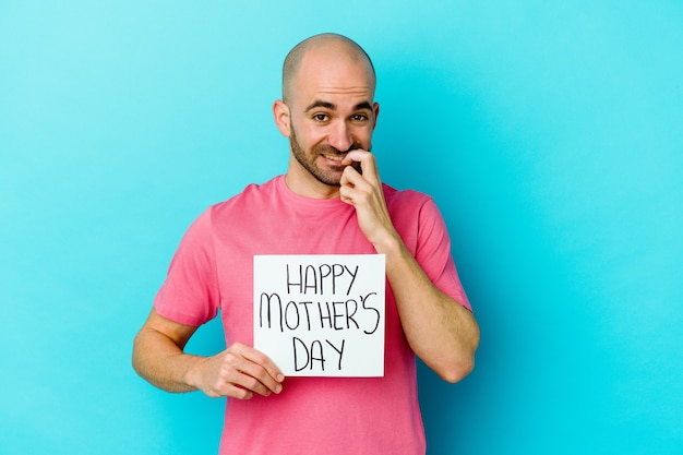 Giovane uomo calvo caucasico che tiene un cartello di giorno di madri felice isolato sulle unghie mordaci della parete blu, nervoso e molto ansioso.